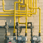 Three gas meters on side of building connected with yellow pipes