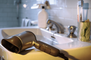Hair dryer resting on bathroom sink ledge