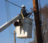 Utility worker in bucket working near power lines