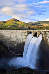Countryside hydrodam with three outlets open releasing water into river below