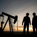 Two oil workers standing near oil drill in predawn light