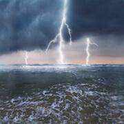 Three lightning strikes over ocean
