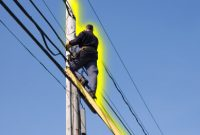Man on ladder working on power lines
